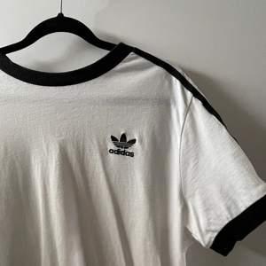 Vit adidas T-shirt med ränderna på sidan, kan va lite genomskinlig. I bra skick