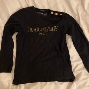 Långärmad äkta Balmain tröja som han köpte i Dubai 2018 tillsammans med skjortan i en annan annons! Hjälper en vän att sälja. Riktigt najs vibe om man stylar rätt. Kan annars vara en najs present till farsan eller brorsan. Köpt för 6000kr, säljes för 2900 kr då kvitto saknas. Vid snabb affär kan priset sänkas
