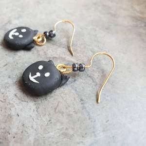 Söta små svarta katter gjorda i lera. Guldiga krokar med två svarta pärlor på.
