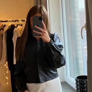 """En supersnygg svart """"skjorta"""" i fakeläder från Zara som jag köpte här på Plick men av mig har den endast använts ca 2 gånger! I storlek S och superbra skick. Den har puffiga detaljer på axlarna och är mjuk på insidan. Funkar bra att ha som den är utan något under eller över ett linne eller liknande 🖤"""