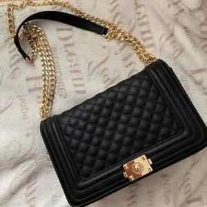 Säljer en svart och guld väska oanvänd, samma skick som den köptes i. Superfint material och allt väldigt rejäl. Ska efterlikna en Chanel väska. Självklart är den fake. Ganska så stor storlek på väskan för att vara en axel-väska, så väldigt rymlig. Säljer för 300 kr. Köparen står för frakten!