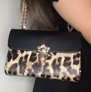 Tvär kattig leopard väska med svarta och guldiga detaljer. Finns ett långt kedjeband som kan användas som långt axelband eller om man dubblar det som kort axelband. Nyskick, använd en gång🐆