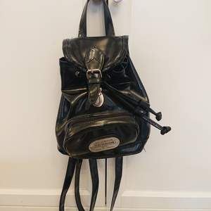 En liten, svart ryggsäck med två extrafickor utanpå i glansigt material. Ganska edgy+stylish men ändå prioriteras min andra ryggsäck varje gång 😒 tror någon annan kommer ha mer glädje av den!