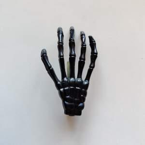 En svart hårklämma som ser ut som en skelett hand och är i bra skick. Vet inte vart den är köpt då jag fått den. Från långfingret på klämman är den 8 cm lång. (Köparen står för frakten)