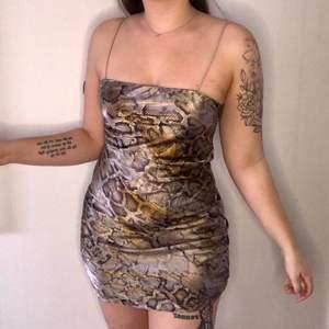 En riktigt snygg fest klänning i orm mönster. Material: silke. Dragkedja på sidan. Använt endast 2 gånger. Säljer pga fel storlek för mig.