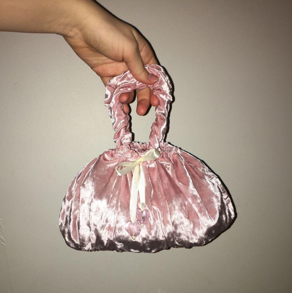 Supersöt liten handväska i återanvänt velourtyg. Väskan är hemmasydd. Handtagen är lite elastiska såsom scrunchies och väskan försluts med ett satinband med hjärtan av glas. Väskan är rymlig och anpassar formen efter innehållet. Önskas mer information ov väskan är du välkommen att kontakta mig. . Väskor.