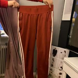 Ett par vinröda Adidasbyxor med fickor fram