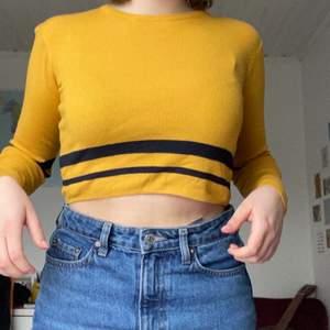 fin solros-gul tröja med två blåa ränder på magen samt armarna. den är lite croppad fast inte jätte. ränderna ser svartare ut i verkligheten. väldigt fint skick.