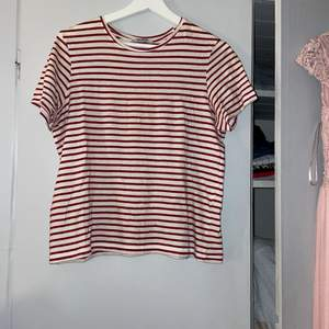 En randig T-shirt. Vin röda ränder och väldigt skönt material. Fint skick! Storlek S men passar XS också! 60kr + frakt🤍