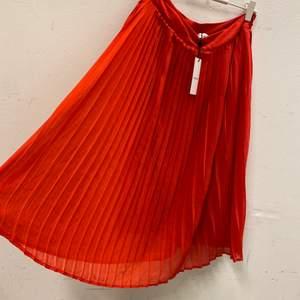 Röd midi-kjol i plisserat tunt, luftigt material. Dragkedja i sidan. Aldrig använd och lappen sitter kvar. Fler bilder kan tas vid önskemål. Frakt tillkommer