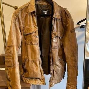 En vintage brun läderjacka. Estimerad vara från runt 1980-talet. Bröstfickor med knapp och sidfickor med dragkedja. Finns 2 innerfickor som stängs med knapp. Den är i bra skick och charmigt sliten. Hämtas i Linköping, kan fraktas inom Sverige, frakt tillkommer.