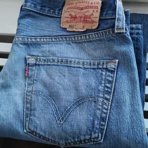 Fina levis 501 jeans i begagnat skick. Det finns slitningar på jeansen både i slutet på benen och ett hål vid låret. (Se bild) annars fint skick. (Jeansen passar tyvärr inte mig så kan inte visa hur de ser ut på.)  Beninnerlängd: 79 cm mätt på golvet. Midjemått sida till sida: 41 cm. Bud från 199 kr! 🤗 Budstopp fredag 20:00. Tar Swish! 💟👖