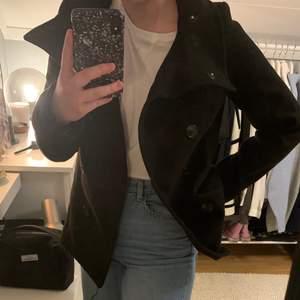 Kort svart kappa från HM. Använd men i fint skick. Två fickor och stängning med knappar. Köpt för 400 kr.