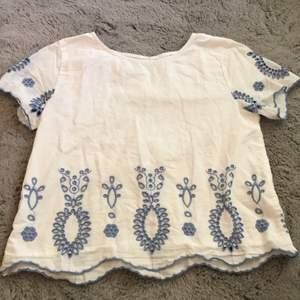 En vit blus med blåa detaljer. I bak på blusen finns det en knapp vid nacken som detalj. Blusen är i bra skick och syns inte att den är använd.