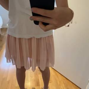 En ljusrosa plisserad kjol från NA-KD. Så fin till sommaren