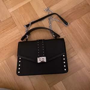 Svart väska i skinn imitation, köpt från något märke i Spanien,  silverkedja och handtag, helt oanvänd