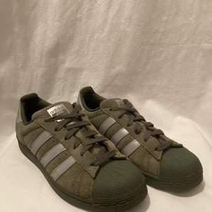 Ett par mörk gröna sneakers i storlek 39/ 39,5 Adidas Superstar med detaljer/ ränder i reflex material. Sparsamt använda därav den fina sulan. ✨  Köparen står för frakten.