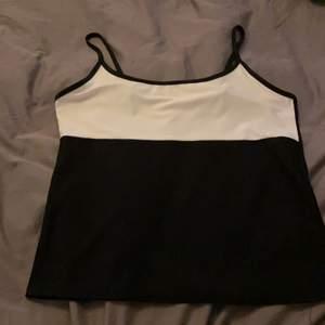 Svart vit linne, helt svart på baksidan, banden är uppsydda