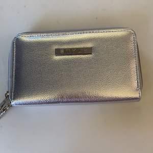 En silvrig plånbok med tre olika fack samt 4 st fack där korten kan vara i. Kan fraktas men då står köparen för den kostnaden.