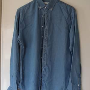 Denimfärgad Slim fit-skjorta från the shirt factory, i klimatsnälla materialet 100% tencell. Snyggt och ruggigt skönt material dessutom. Hade gärna haft den kvar, men krympte efter första tvätten. Strl 40. Känns som en Medium