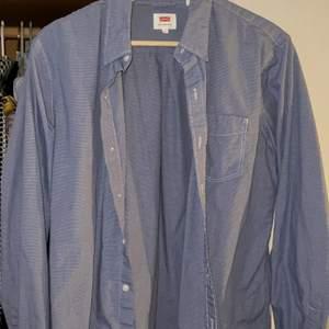 En ljusblå levi's skjorta som har små vita rutor på sig! herr modell men haft den som en oversize skjorta! Super snygg