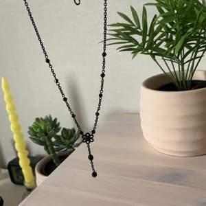 """Svart halsband med en blomma och en liten hängande """"charm"""".                                                                                     Säljes pga inte min stil längre.                                                 20kr+frakt"""