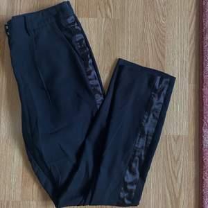 Svarta kostymbyxor med fin detalj!  Kostymbyxor från Forever 21, köpta i USA. Fin detalj längs sidorna i silkesliknande material. Med bälteshällor, fickor framtill och fejkfickor baktill.   Välanvända men mycket kvar att ge!   Material: 100% polyester   Köparen betalar frakten☀️