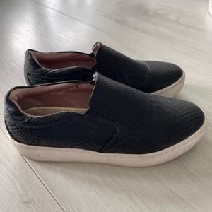Säljer dessa trendiga svarta slip on skor med fejk ormskinnsmönster. Skorna är ifrån XIT och jag har använt dem några fåtal gånger. Superfint skick! Storlek 37. Pris kan diskuteras. 💓