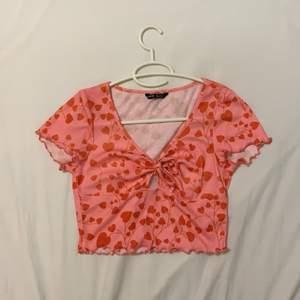 Rosa tröja med röda hjärtan på i storlek medium. Har bara testats:)