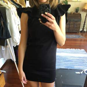Black mini dress in sweat fabric with cut out back. Very short and sexy dress but still casual because of the fabric.