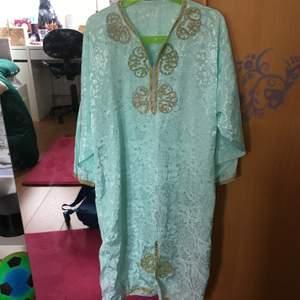 En turkos orientalisk klänning. Kan användas till maskerad. Skulle säga att det är storlek XS. Köparen står för frakten
