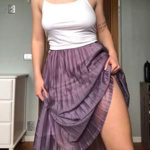 Så fin och somrig lila kjol i ett glittrigt nylontyg på yttre lagret. Resår i midjan så passar de flesta storlekarna. Plisserad/veckad. Nyskick endast använd ett fåtal gånger
