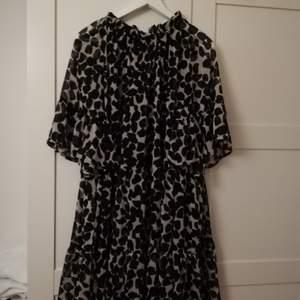 Luftig och lös klänning med svarta fläckar på benvit bakgrund. Har knytning i nacken. Jag har haft den på mig 2 ggr med svart skärp.