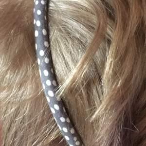 Grått hårband med vita prickar på