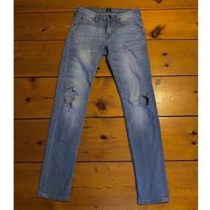 Blåa lee jeans med egenklippta hål vid knäna