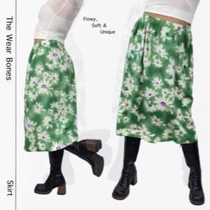 Supersöt och unik thrift flip mid kjol med grönt, blommigt material. I toppenskick! Bandet är elastiskt, sytt lite vridet så på insidan av bandet vrids ett varv runt, syns på sista bilden. En fläck finns men är nästa så den ser ut att vara en del av printet. Det finns ingen underkjol. Modellen använder storlek S och  är 169cm. Kolla gärna måtten nedanför. Midje bredd (mätt medan kjolen ligger ner utan att töjas ut) 40cm och längd 74cm. Ingen retur eller refund.  Spårbar frakt på 66kr är inräknad i priset och SafePay tar 10% av betalningen. Tyvärr kostar det lite extra då jag alltid kommer skicka spårbart och använda SafePay för bådas säkerhet