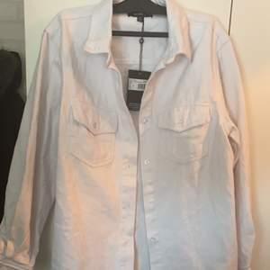Snygg vit oversize skjorta i denim i storlek 34. Helt ny med lappen kvar, endast testad! Frakt tillkommer.