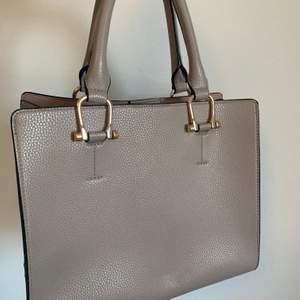 Stor och fin beige väska från H&M. Nästan helt oanvänd, fint skick! Tre större fickor och fler mindre i mitten fickan.