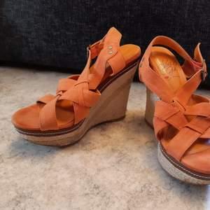Somriga kilklackar i orange mocka. Använda en gång på skolavslutning. Klackhöjd 12 cm, platåhöjd ca. 4 cm. Storlek 36.