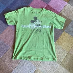 Grön Disney T-shirt med Musse Pigg motiv i stolek medium. Liten missfärgning (se den tredje bilden). Frakt ingår i priset.