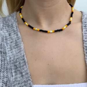Svart pärlhalsband med gula och orangea pärlor🖤🤍🧡💛 halsbandet försluts med lås och tråden är elastisk
