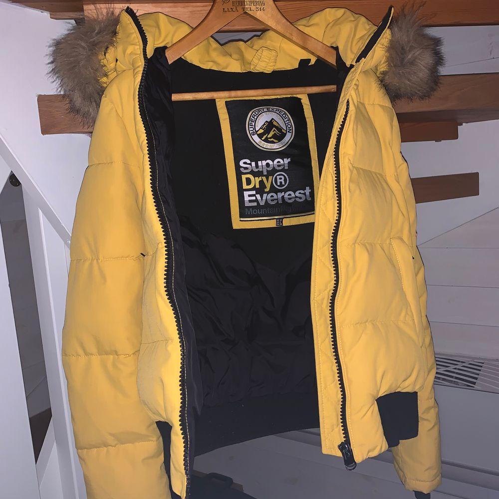 En gul dunjacka från Superdry. Huvan / Kapuschongen går att ta av och på beroende på hur man vill ha jackan. Köpt för flera år sedan och säljer då jag har köpt en ny jacka :)             ✨Priset går att diskutera ✨. Jackor.