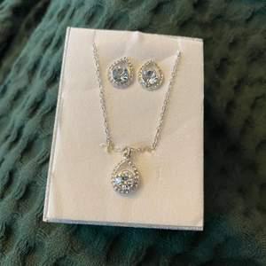 Ett set med halsband och örhängen i en silver-glittrig ask. Aldrig använda. Fler bilder kan tas vid önskemål. Frakt tillkommer.