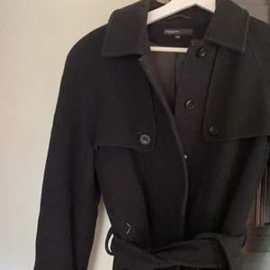Så snygg svart kappa med detaljer vid bröstet