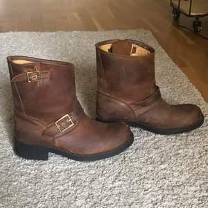 Ett par bruna boots som säljs för att de inte har används på väldigt länge. Riktigt läder, guldiga spännen och 3cm klack. Skorna är lite slitna som ni ser men inga hål eller stora märken. Funkar bra på höst, vår och sommar men skulle inte säga att det är vinter skor för det är inte fodrade. OBS! Köparen står för frakt om vi inte möts upp i Sthlm:))))