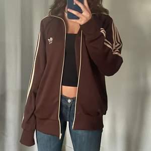 Så snygg zip up hoodie från adidas. Jättefin brun färg med beiga detaljer, storlek XL men sitter fint oversized på mig som brukar ha S. Så bekväm och passar så bra som en tjockare tröja på sommarkvällar! Jättefint skick! Om fler är intresserade så blir det budgivning 🤎🤎
