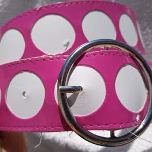 Rosa retro bälte med stora vita prickar och cirkelformat silverspänne. Materialet är glansig vinyl. Sparsamt använt. 100 cm långt och4 cm brett.