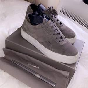 Gråa Axel arigato skor i mocka. Använda ca.3 gånger! Köptes från deras butik i Stockholm. Storlek 38. Box och Dustbag tillkommer!