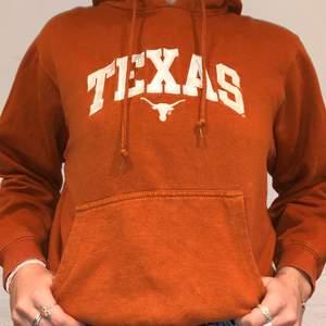 Vi säljer denna brun/orangea Texas hoodie. Priset är 279kr. Den är i storlek M men passar som en S/XS. Personen på bilden är 175 och brukar ha på sig S/M. Inga defekter på hoodien.  Kontakta oss på Plick eller på vår Instagram @wanderetro. Om flera visar intresse blir det budgivning. Köparen står för spårbar frakt på 66kr. 🤍