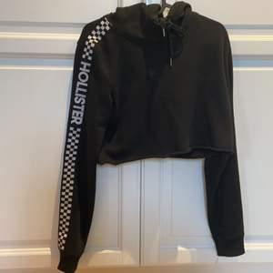 En croppad svart hollister hoodie. Knappt använd därför säljer jag den. Rutade streck på båda sidor med text hollister. Skriv för mer frågor💖